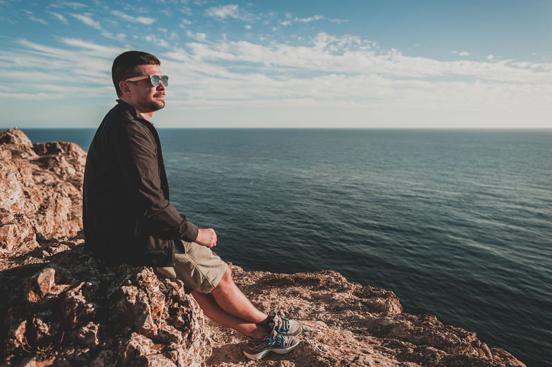 Man sitting on rock by sea against sky