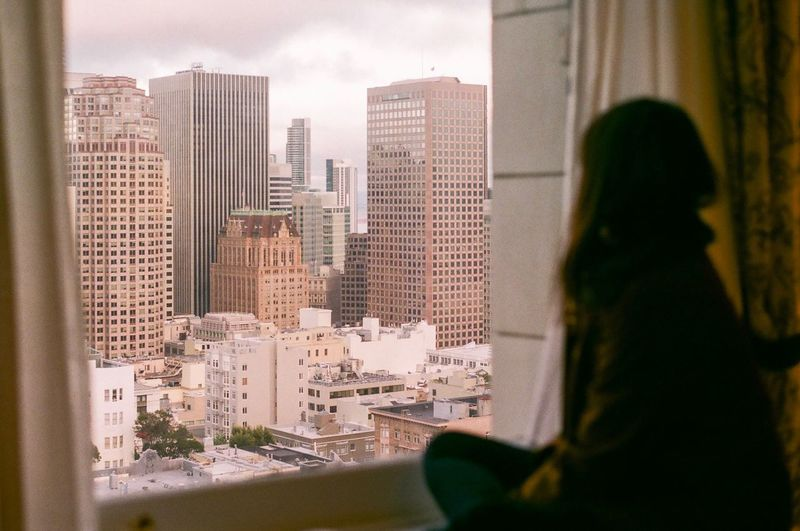 Woman looking at cityscape through window