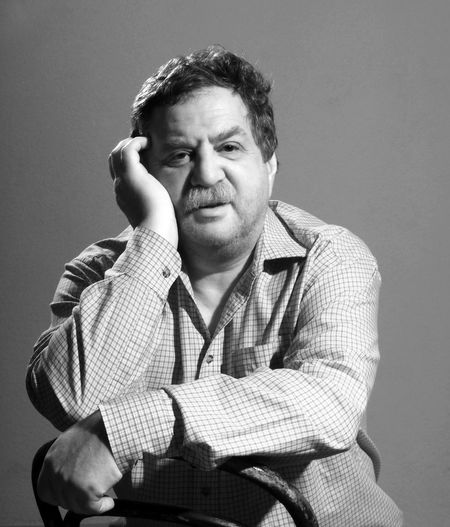 Portrait of mature man sitting on chair against wall