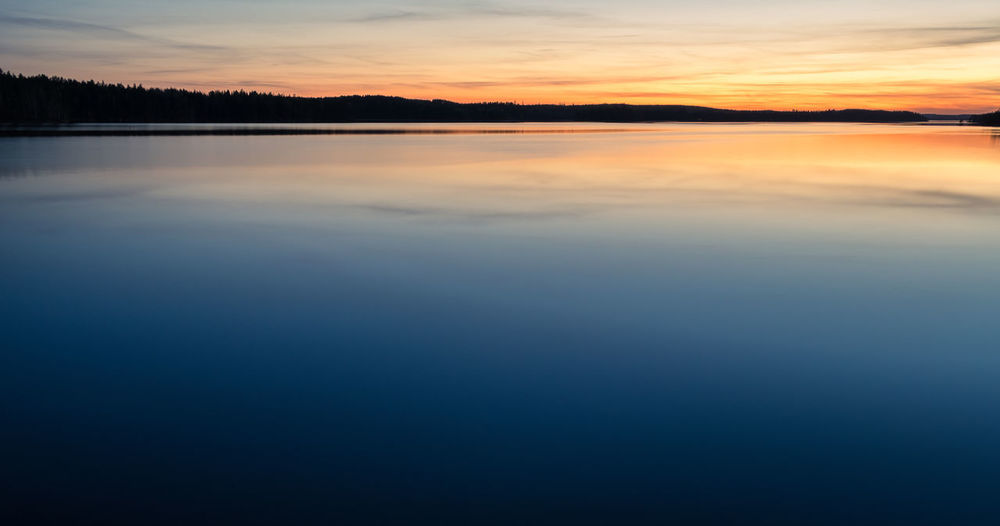 Scenic dawn landscape with lake after sunset at spring evening in Finland Scenics - Nature Tranquility Beauty In Nature Water Sky Tranquil Scene Lake Sunset Cloud - Sky Reflection Waterfront No People Idyllic Nature Orange Color Non-urban Scene Copy Space Silhouette Outdoors Twilight Landscape Reflection Finland Nature Standing Water