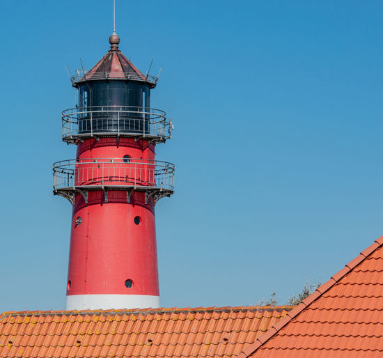 Roof by lighthouse against clear blue sky
