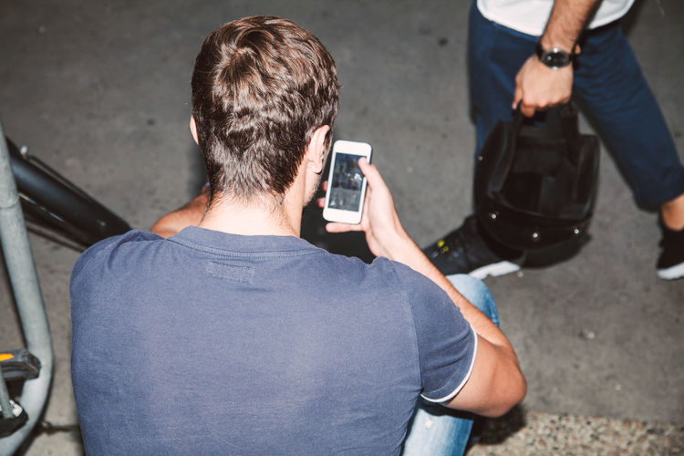 Rear View Of Young Man Using Mobile Phone While Sitting On Steps