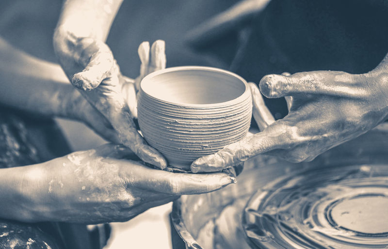 Old vintage photo. a raw clay pot in the hands of a potter. workshop in the pottery workshop