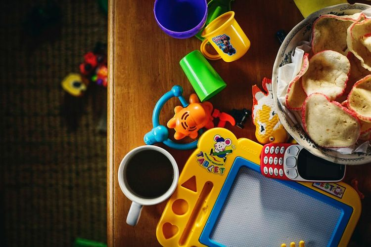 A mug of coffee, fish cracker, phone and lots of toy. Coffee Time Coffee - Drink Coffee Break Light Light And Shadow Coffee Fish Crackers Toy Toys Mess Scattered Table High Angle View Indoors  Food No People Sweet Food Day Colour Your Horizn