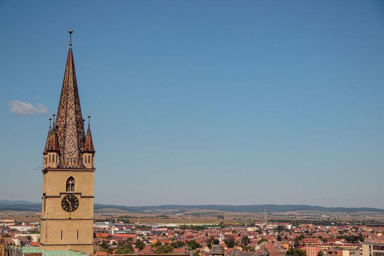Tower amidst buildings against blue sky