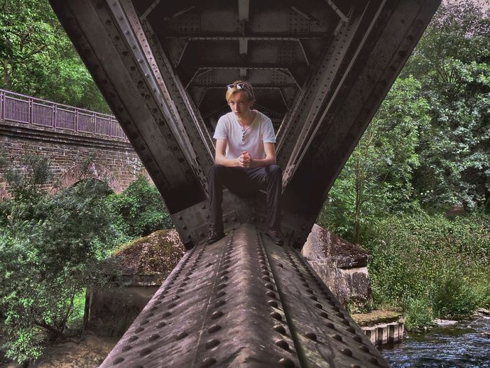 Portrait of young man sitting on bridge over river