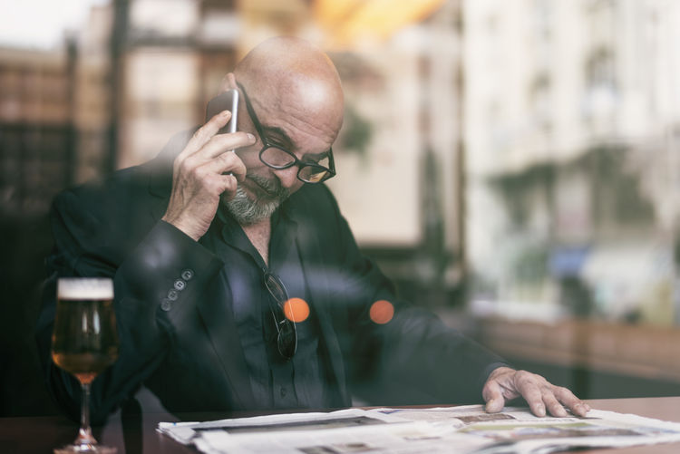 Bald businessman with newspaper on table talking over smart phone in cafe seen through window
