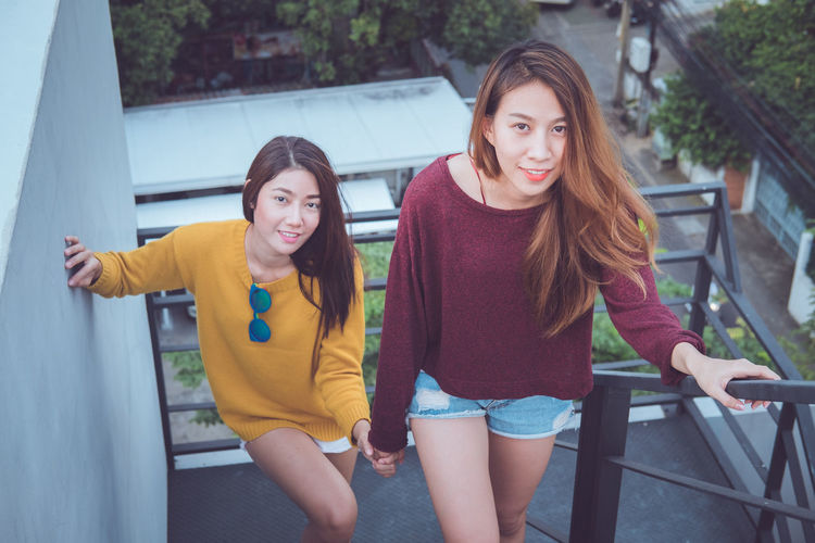Lovely lesbian couple together concept. Couple of young asian women walking up the stairs to top roof. Adult Architecture Casual Clothing Day Friendship Front View Full Length Leisure Activity Lifestyles Outdoors People Real People Sitting Smiling Three Quarter Length Togetherness Two People Young Adult Young Women