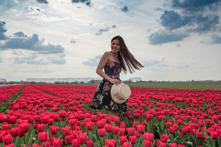 Portrait of woman standing by blooming tulips