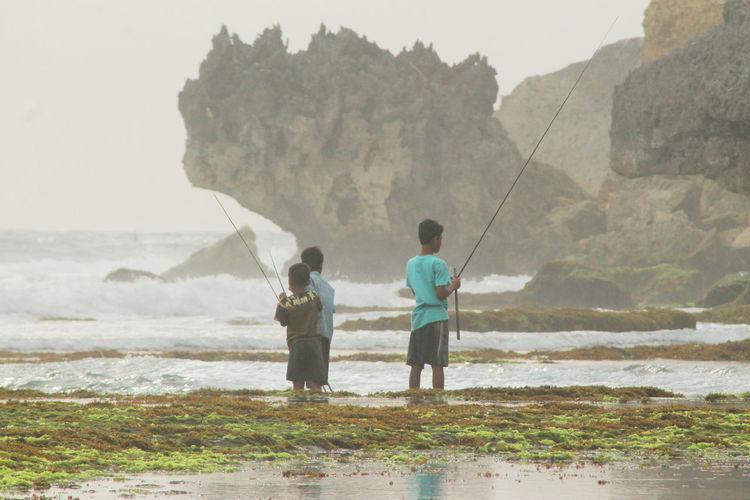 Boys fishing in sea against sky