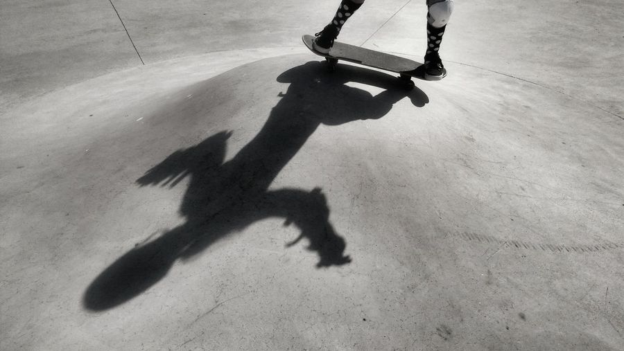 Low section of person skateboarding by shadow at park
