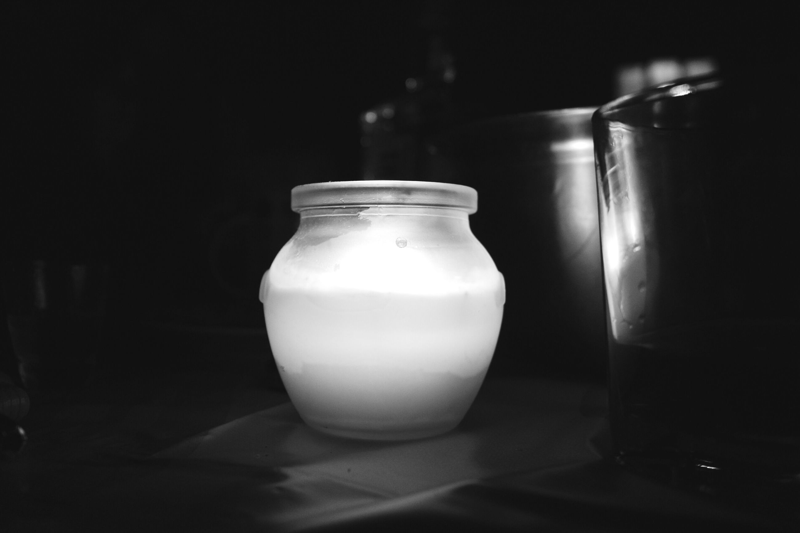 indoors, illuminated, still life, close-up, candle, table, lighting equipment, glass - material, home interior, glowing, lit, focus on foreground, electricity, no people, transparent, flame, jar, bottle, light bulb, light - natural phenomenon