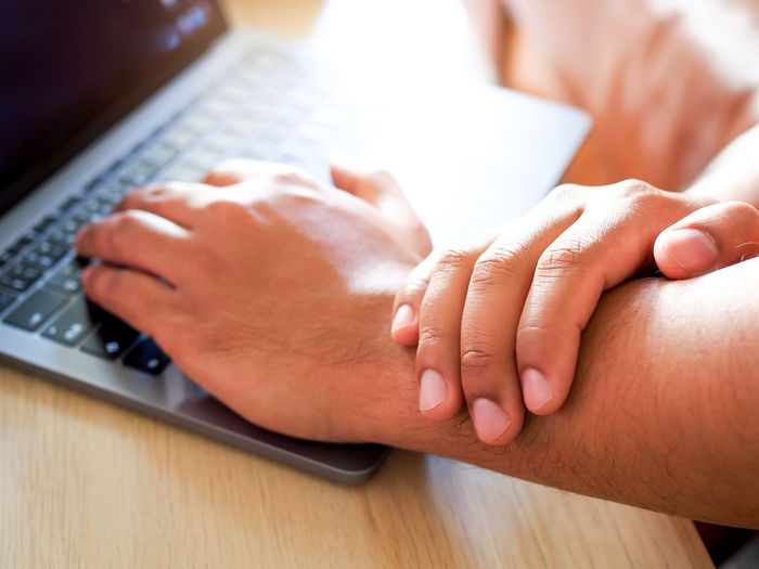Cropped hand holding hand while using laptop at office