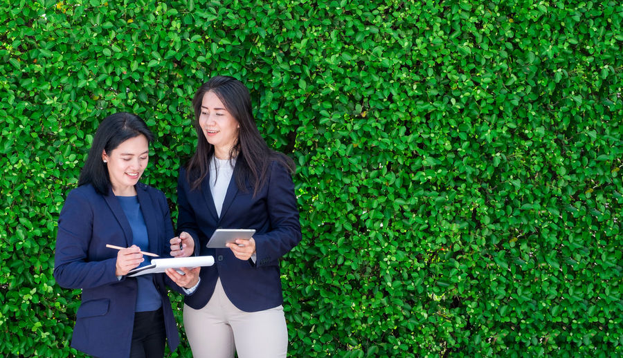 Two asian businesswoman taking about work outside office at green leaves hedge Business Copy Space Nature Suit Tablet Wall Business Businesswoman Communication Connection Corporate Business Ecology Females Hedge Leadership Meeting Outdoors Partnership - Teamwork Teamwork Technology Togetherness Two People Well-dressed Women Working