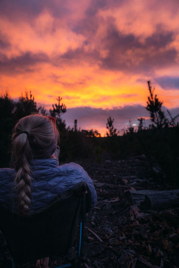 Rear view of woman sitting on field against sky during sunset