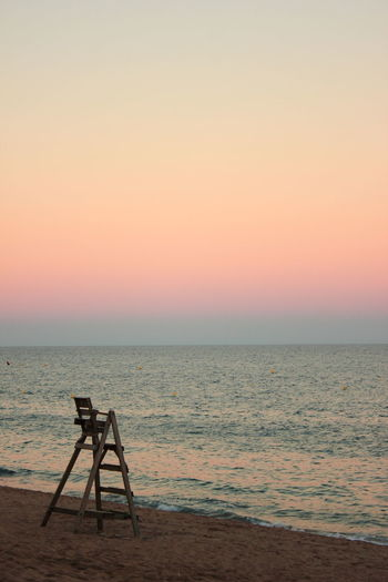 Lifeguard chair at beach against clear sky during sunset