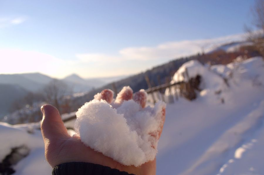 Winter motifs. Snow in the men's hand closeup. Enjoying a beautiful and sunny winter day. Beauty In Nature Close-up Cold Temperature Day December Human Hand January Landscape Leisure Activity Mountain Nature One Man Only One Person Outdoors People Real People Scenics Sky Snow Winter