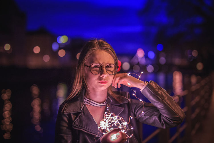 Portrait of young woman holding illuminated string lights by lake at night