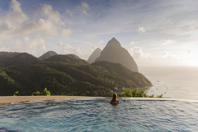 Scenic view of infinity pool with woman relaxing against sky