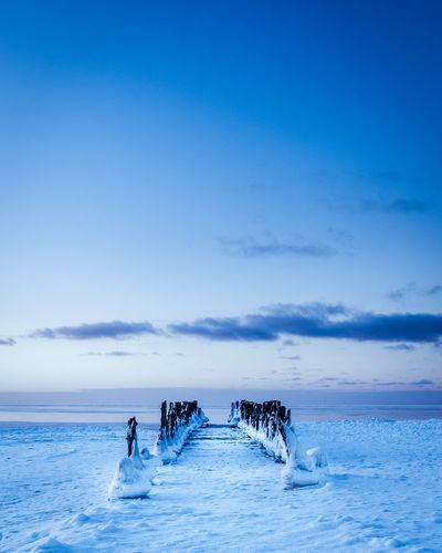 People in sea against blue sky
