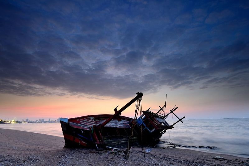 Abandoned fishing boat on beach against sky during sunset