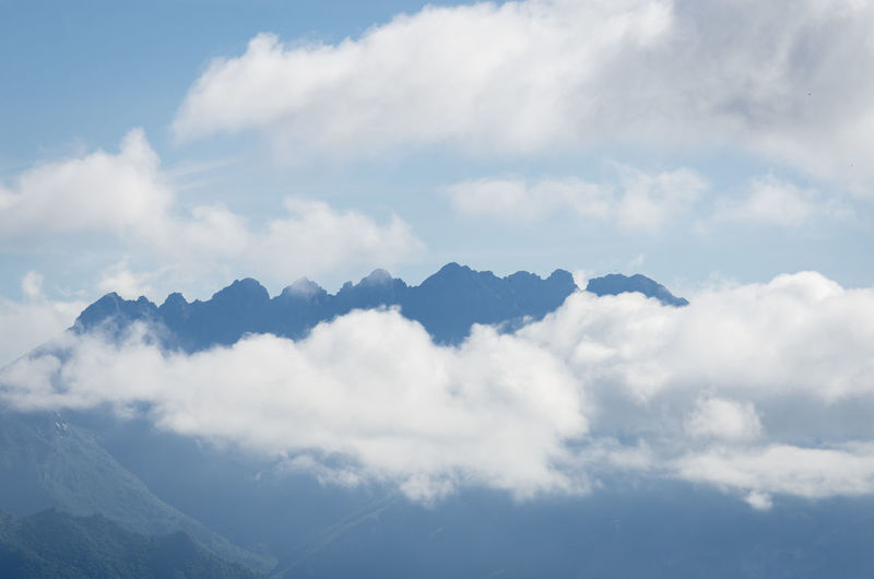 Low angle view of clouds over mountains against sky