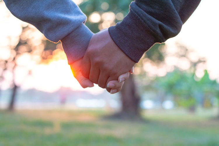 Cropped image of couple holding hands in park