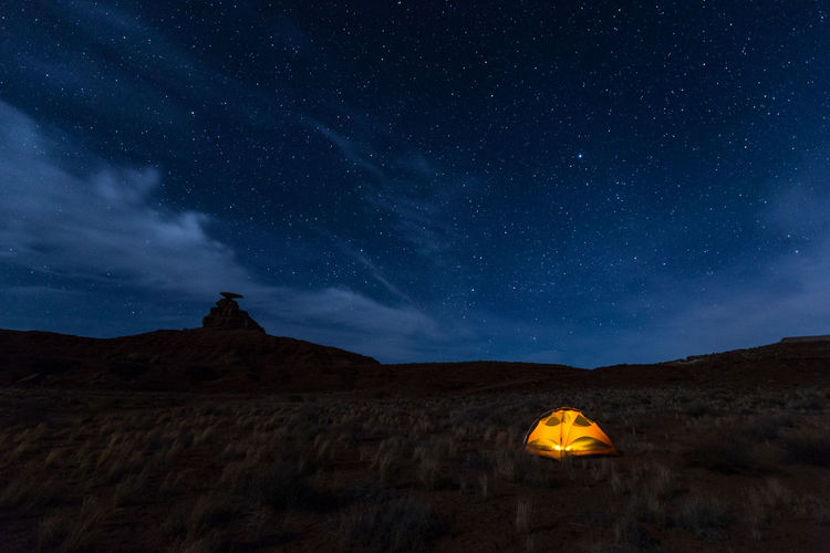Scenic view of illuminated tent on field against sky at night