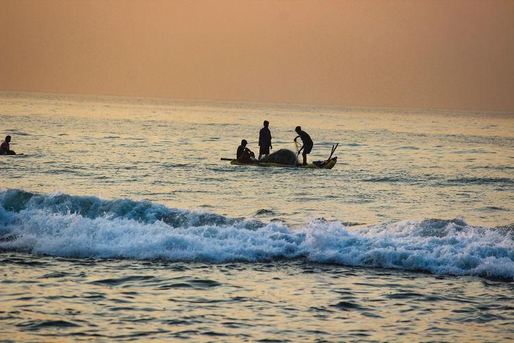 People fishing on sea during sunset