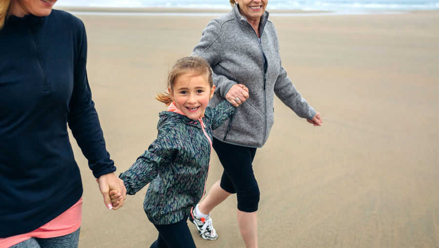 Playful Woman Walking With Mother And Daughter At Beach