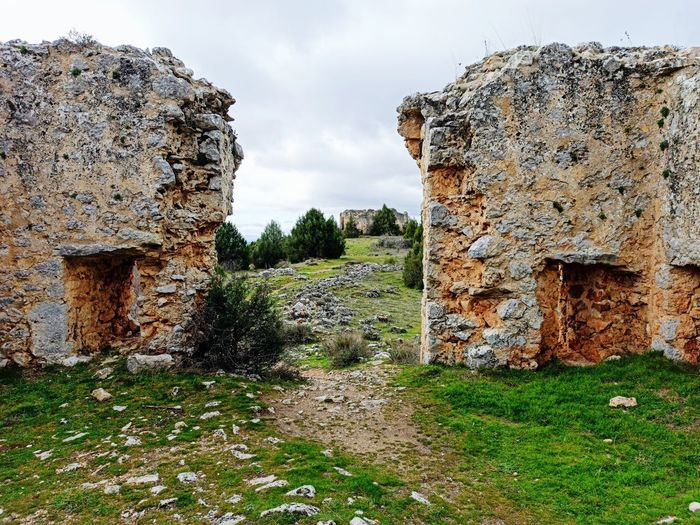 Old ruins on field against sky
