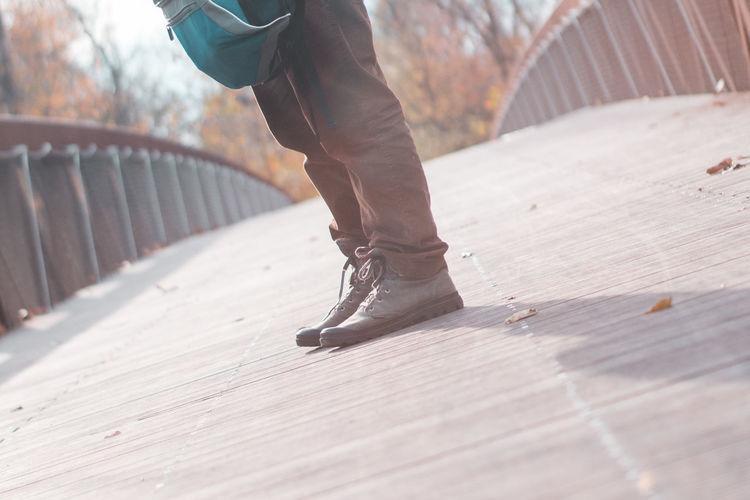 Low section of man standing on footbridge