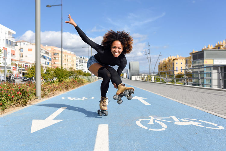 Young fit black woman on roller skates riding outdoors on urban street. Smiling girl with afro hairstyle rollerblading on sunny day City Fun Happiness Leisure Activity Lifestyles Looking At Camera Motion One Person Outdoors People Portrait Real People Rollerblading Rollerskating Skater Skatergirl Skating Sky Smiling Young Adult Young Women