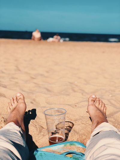 Low section of man relaxing at beach