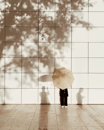 Woman with umbrella standing against building