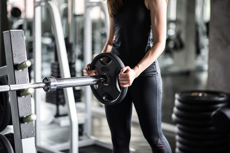 Midsection of young woman exercising in gym