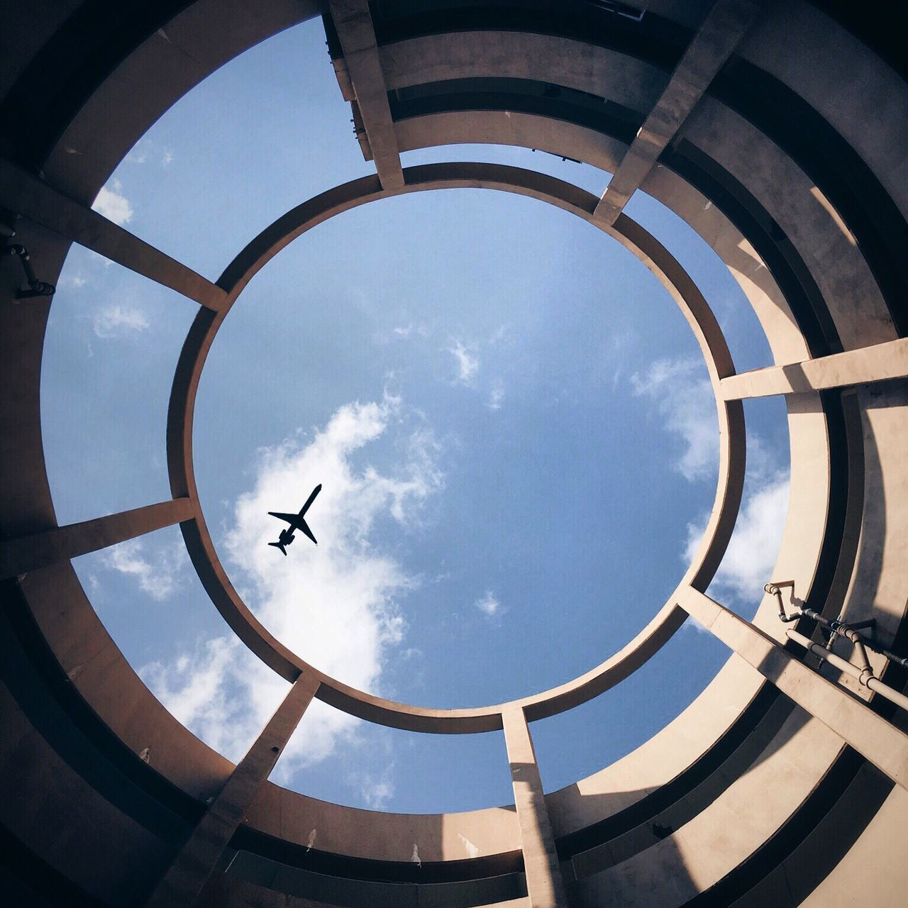 Directly below shot of silhouette airplane seen through building