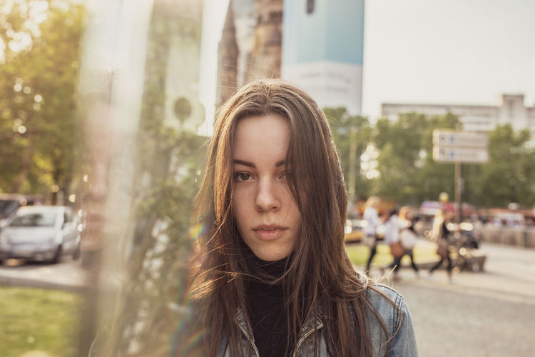 Portrait of beautiful young woman standing by glass in city