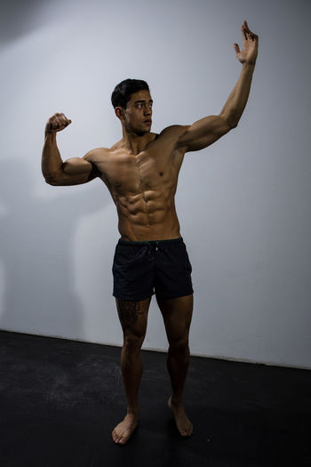 Muscular male fitness model posing behind a grey wall. Full body shot. Adult Asian  Athlete Body & Fitness Human Body Man Nam Vo Shirtless Sportsman Arms Raised Fitness Model Full Body Shot Grey Wall Handsome Hunk Male Muscle Muscular Build One Person Pose Posing Strength Strong Studio Shot Torso