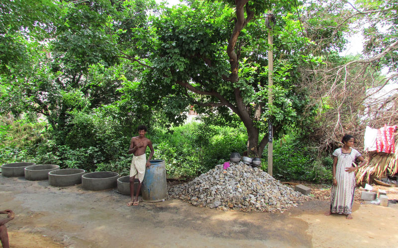 MAN AND WOMAN kitchen utensils Watercan Man And Woman Standing Heap Of Stones Cement Rings Hut Shirtless !  Poverty But Happiness Jungle Woman Man Tree