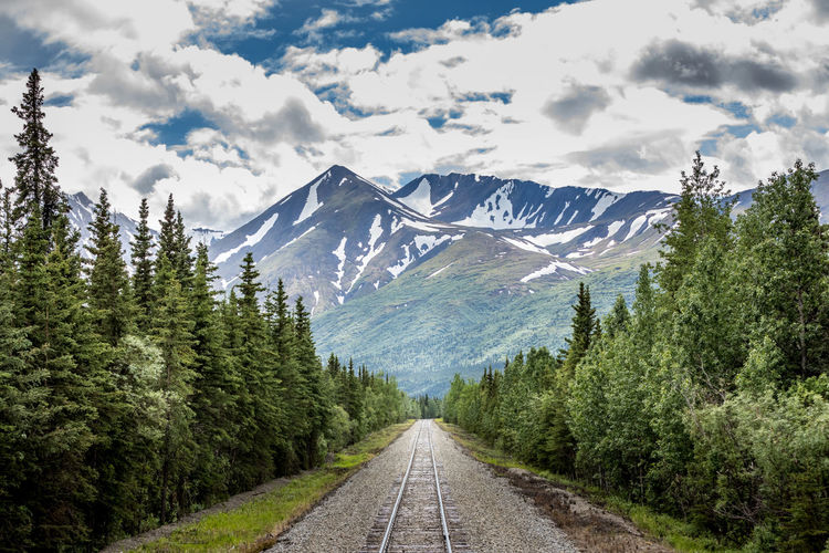 Railroad tracks leading towards mountains against sky