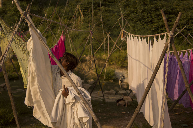 EyeEm Selects Hanging Clothesline Drying Outdoors Adult Tree Day People Dhobie Ghat Laundrymen Dhobi Summer Drying Clothes