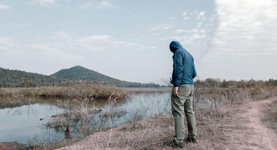 Full length of man standing by lake against sky