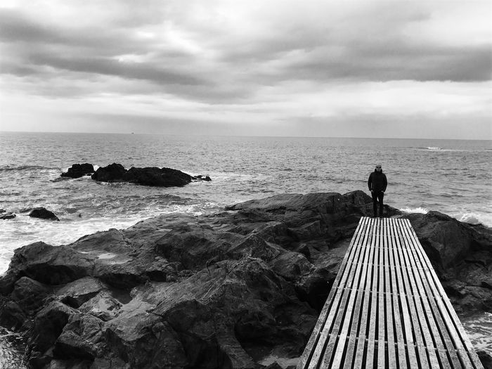 Man standing on sea shore against sky