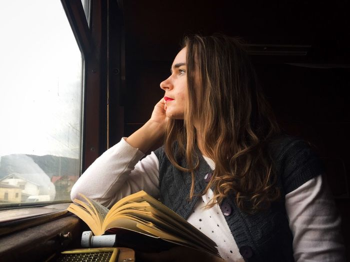 Young woman looking through window while traveling in train