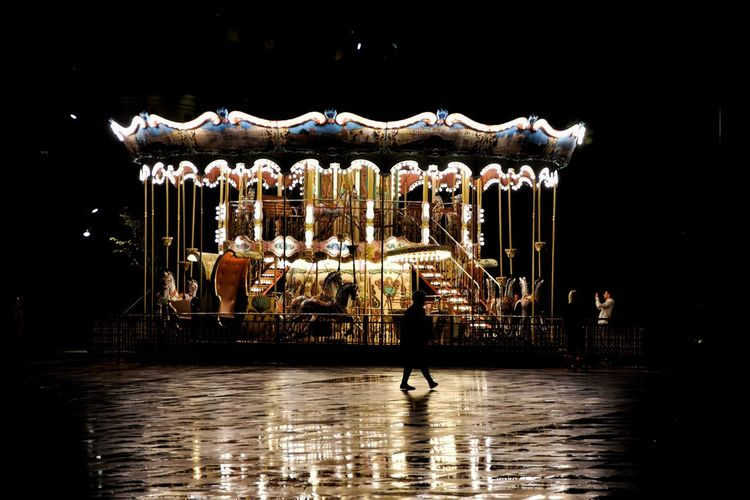 Silhouette Woman Walking Against Illuminated Carousel At Night