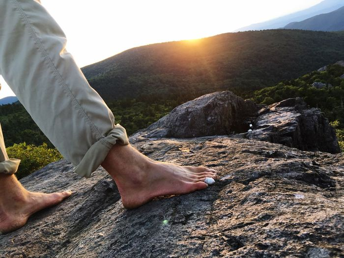 Low section of man on rock against sky