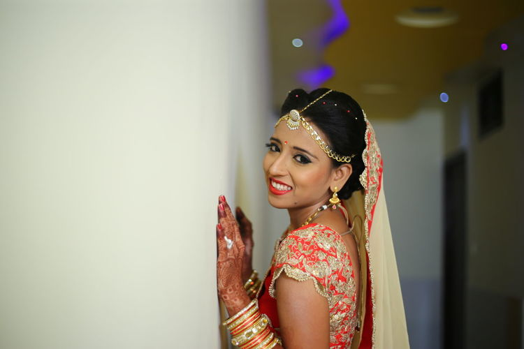 Side View Of Bride Standing By Wall In Corridor