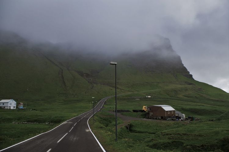 gasadalur on the faroe islands. Beauty In Nature Day Extreme Weather Faroe Islands Fog Foggy Gasadalur Island Mountain Mountains Nature No People Ocean Outdoors Power Line  Remote Road Rural Scene Scenics Sea Social Issues Street Light Thunderstorm Traffic Lights Uphill