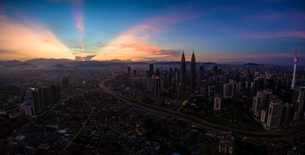 Aerial view of Kuala Lumpur during sunrise with ray of light in background Aerial View Architecture Blue Built Structure Capital Cities  City City Life Cityscape Cloud Cloud - Sky Dramatic Sky Horizon Over Land Illuminated Landscape Modern Nature No People Orange Color Outdoors Residential District Scenics Sky Sunset Travel Destinations Wide